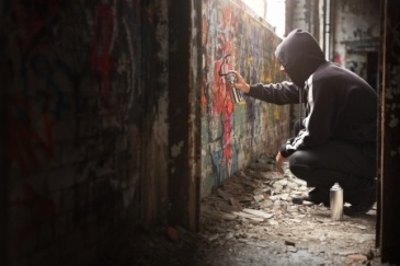 graffiti artist spraying a wall