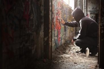 graffiti artist spraying a wall
